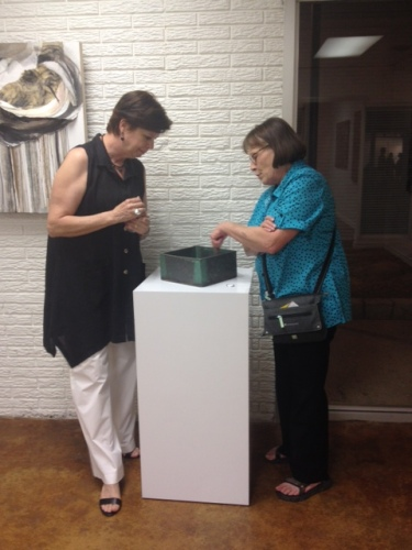 Rebecca Boaman (r) is explaining one of her 3D pieces to Kimberly Reid (l).